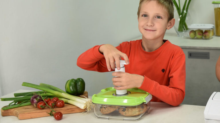 a boy vacuum packing food in a container