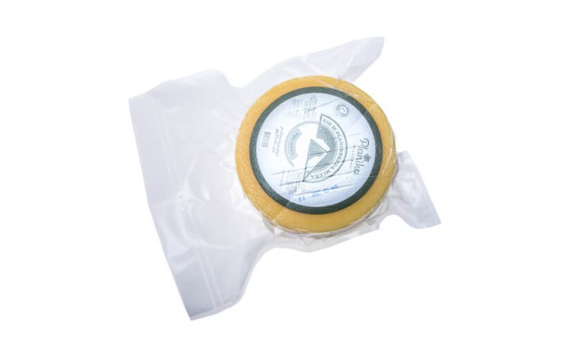 Vacuum packed wheel of cheese for sales and transport.